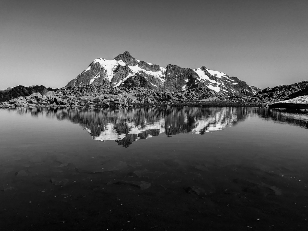 Mount Shuksan reflected on an almost still mountain tarn