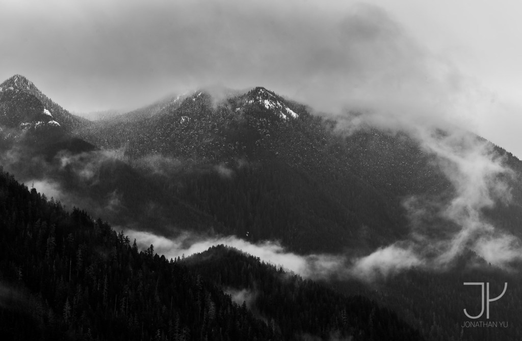 Clouds dance around low hanging peaks, leaving the seasons first snow