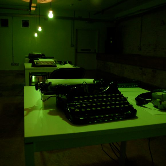 A row of green typewriters stretches off into the distance underneath a low of bare lightbulbs