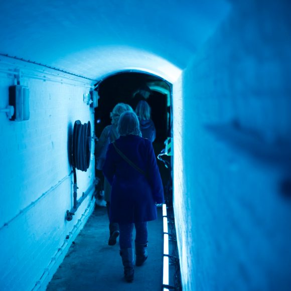 People walking through a corridor underneath Tower Bridge, bathed in blue light