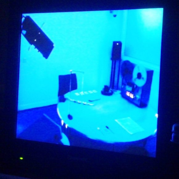 CCTV footage of a room. We see a table, a reel-to-reel tape player and scientific equipment
