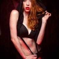 Redhead fashion model dressed in long black hoodie and underwear