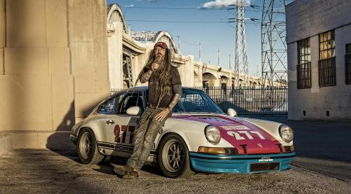 Magnus Walker leans against his 277 Porsche rac car under the 6th street bridge in Los Angeles