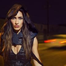 Portrait of brunette model on city street at night wearing leather clothing.