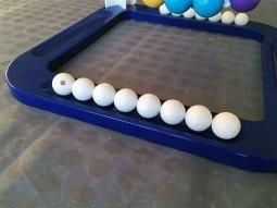 Le but du jeu est de placer en équilibre toutes ses boules blanches sur la grappe de boules de couleurs.