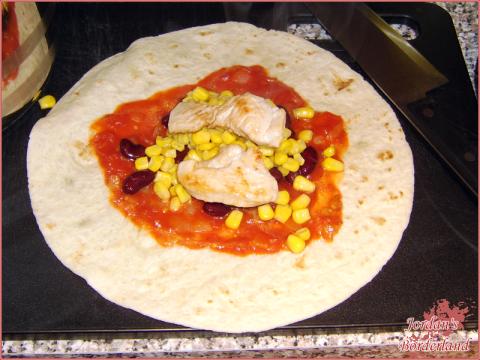 Tortillia mit Putenbrust, Sauce, Mais und Kidneybohnen füllen
