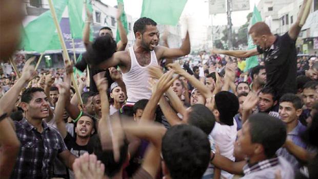 Com bandeiras verdes do Hamas, jovens celebram na Faixa de Gaza acordo de cessar-fogo duradouro assinado por autoridades palestinas e de Israel no Cairo
