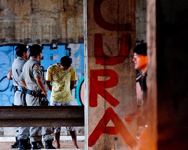 Jovem usuário de drogas algemado ao lado de uma pichação que diz aquilo que a grande parte dos dependentes procura: cura | Foto: Renan Accioly