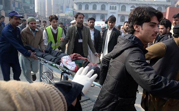 Voluntários paquistaneses carregam estudante ferido em Peshawar: ataque talibã deixou pelo menos 130 mortos em escola militar no Paquistão Foto: A majeed AFP