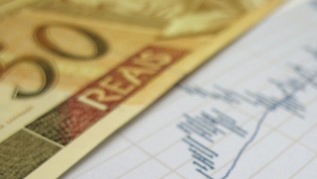 Stock market charts for investor analysis, with Brazilian Real $50 bills and pen, using selective focus on graph and pen.