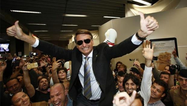 """Jair Bolsonaro, vestido de """"Bolsomito"""" e carregado pelo lutador Wanderlei Silva (à esquerda): chegada triunfal do salvador da pátria que só pode ser Messias no nome"""