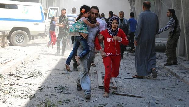 Família síria corre para se esconder no meio dos escombros de edifícios destruídos na sequência de um ataque aéreo relatado em Aleppo, em 29 de abril