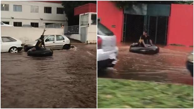 Homem se diverte em boia durante enxurrada em avenida de Goiânia