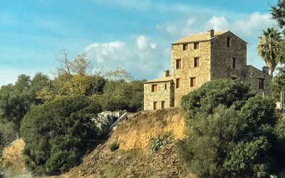 Traditional granite farmhouses rise from the scrubland.