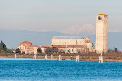 On the island of Torcello, the Basilica di Santa Maria Assunta and adjoining Byzantine-style church of Santa Fosca stand out against the snowy mainland backdrop of the Dolomites mountains