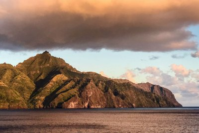 The setting sun turns Nuku Hiva into a mountain of bronze.