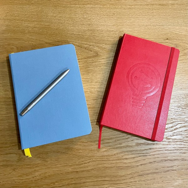 A red and blue notebook on an oak table