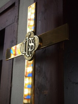 The stained-glass windows are reflected on the surface of a golden cross at St. Paul's Episcopal Church in Ironton, Mo.