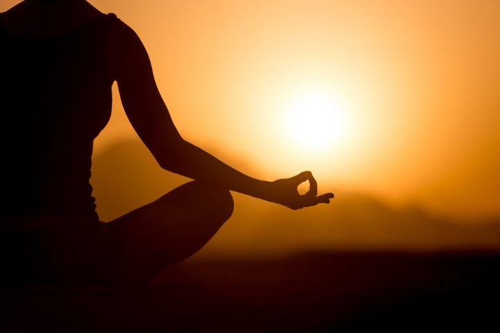 Silhouette of young woman sitting cross-legged with fingers in yogic Jnana mudra. Relaxation, meditation in beautiful mountainous landscape at sunset or sunrise, close up, copy space