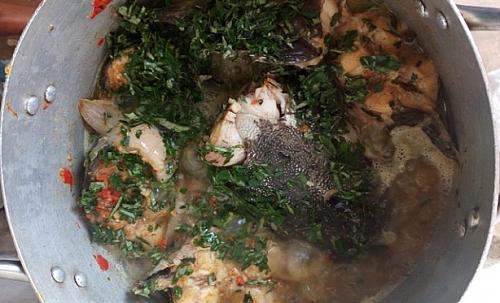 Adding of uziza leaves to catfish pepper soup