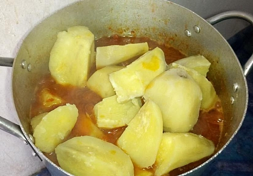 Adding of boiled sweet potatoes to tomato sauce