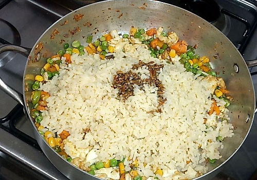 Stir in the cooked rice to combine and season with soy/ oyster sauce