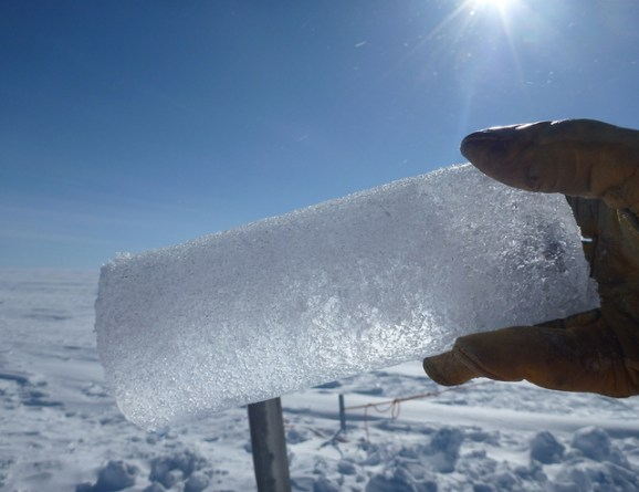 A 25-cm long ice core is held in front of the camera on a sunny day. The background is an endless snow-covered flat landscape and a bright blue sky.