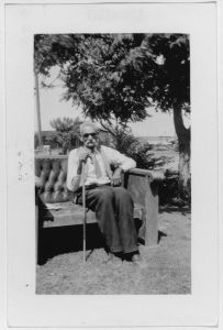 Elderly African American man seated in a chair with a cane.