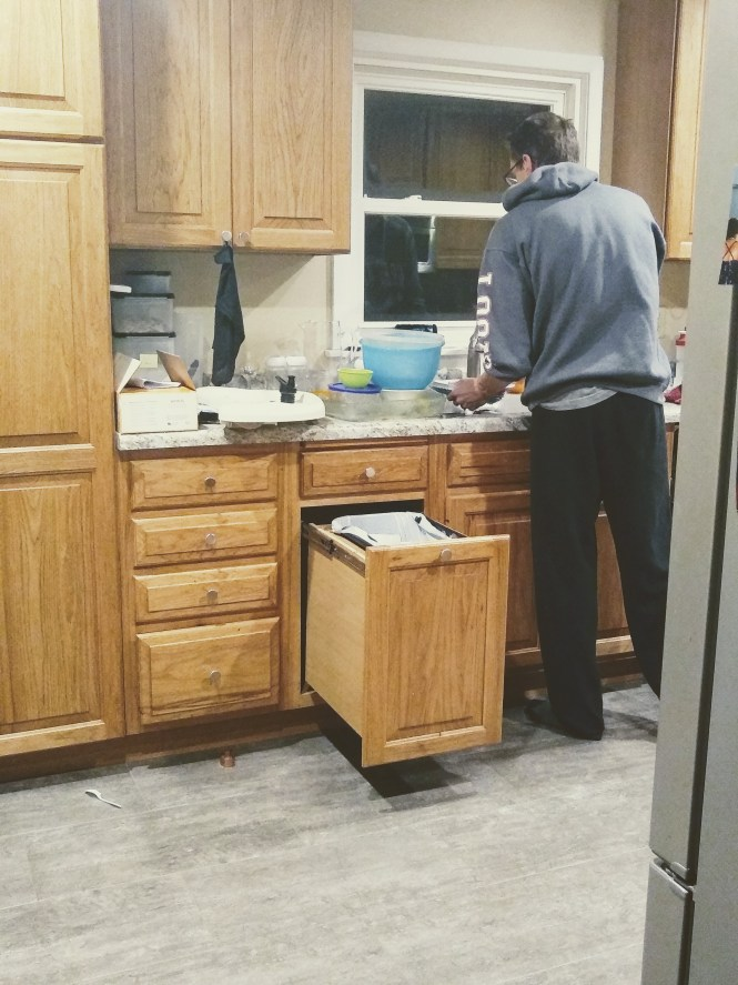 A husband selflessly doing the dishes in the early morning hours.
