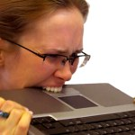 woman biting laptop