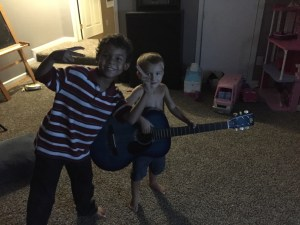 """Malachi and one of our """"adopted brothers"""" during family devotions (and No, Malachi is not a prodigy at guitar...he just THINKS he is)"""