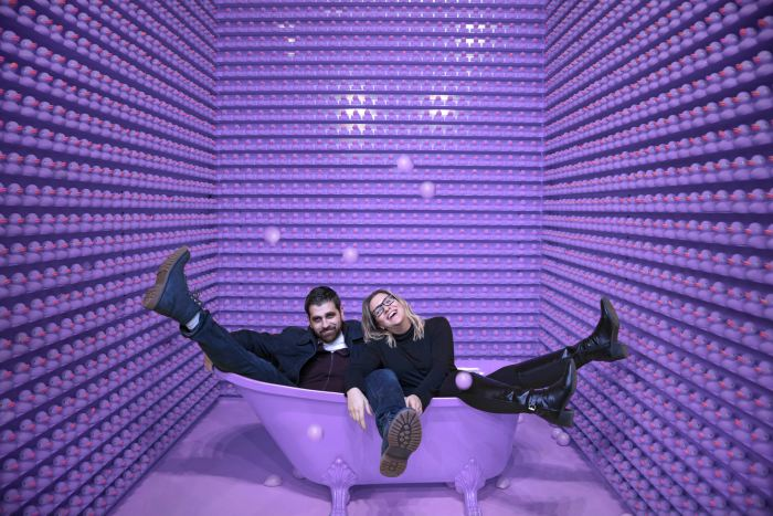 Two people sat in a bath in a room filled with purple rubber ducks.