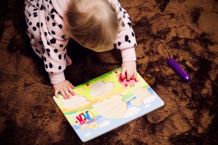 A small child looking at a wooden puzzle.