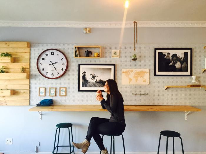 A woman at a coffee shop with a clock in the background