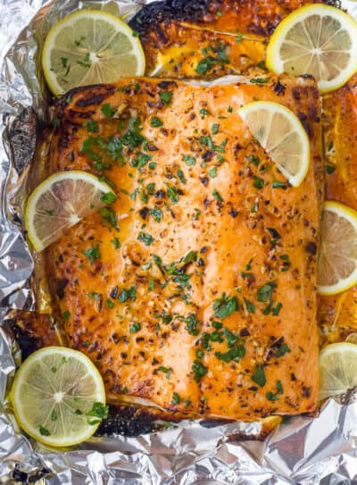 overhead photo of garlic butter baked salmon in foil with lemons on top