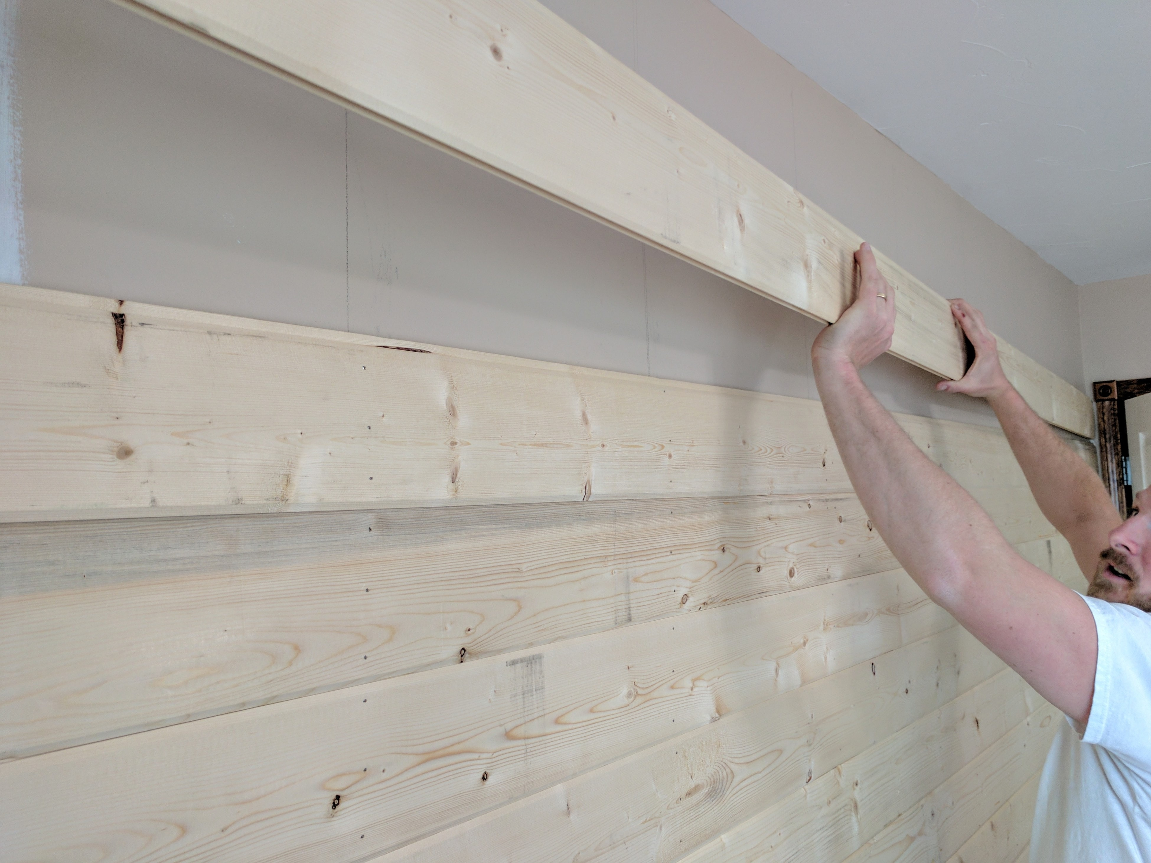 A Man Installing A Board For A DIY Wood Plank Accent Wall