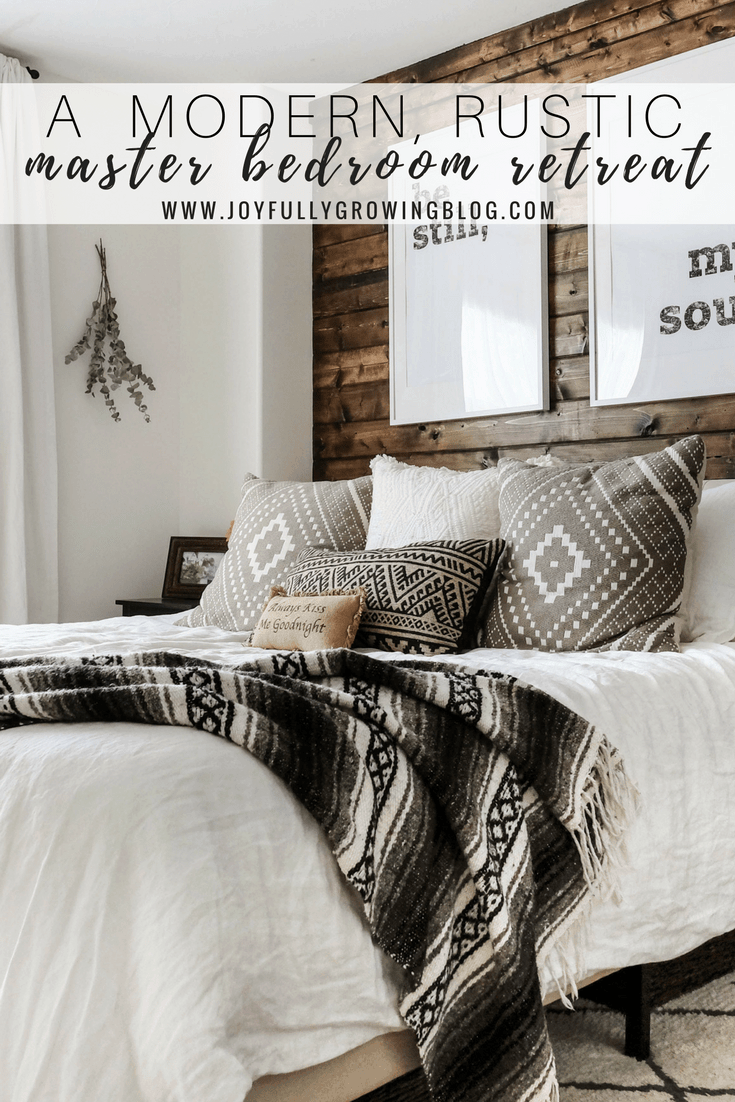 """A rustic bedroom with a closeup of the bedding including throw pillows and blanket, up against a wood plank wall. Text overlay """"A Modern, Rustic Master Bedroom Retreat - www.joyfullygrowingblog.com"""""""