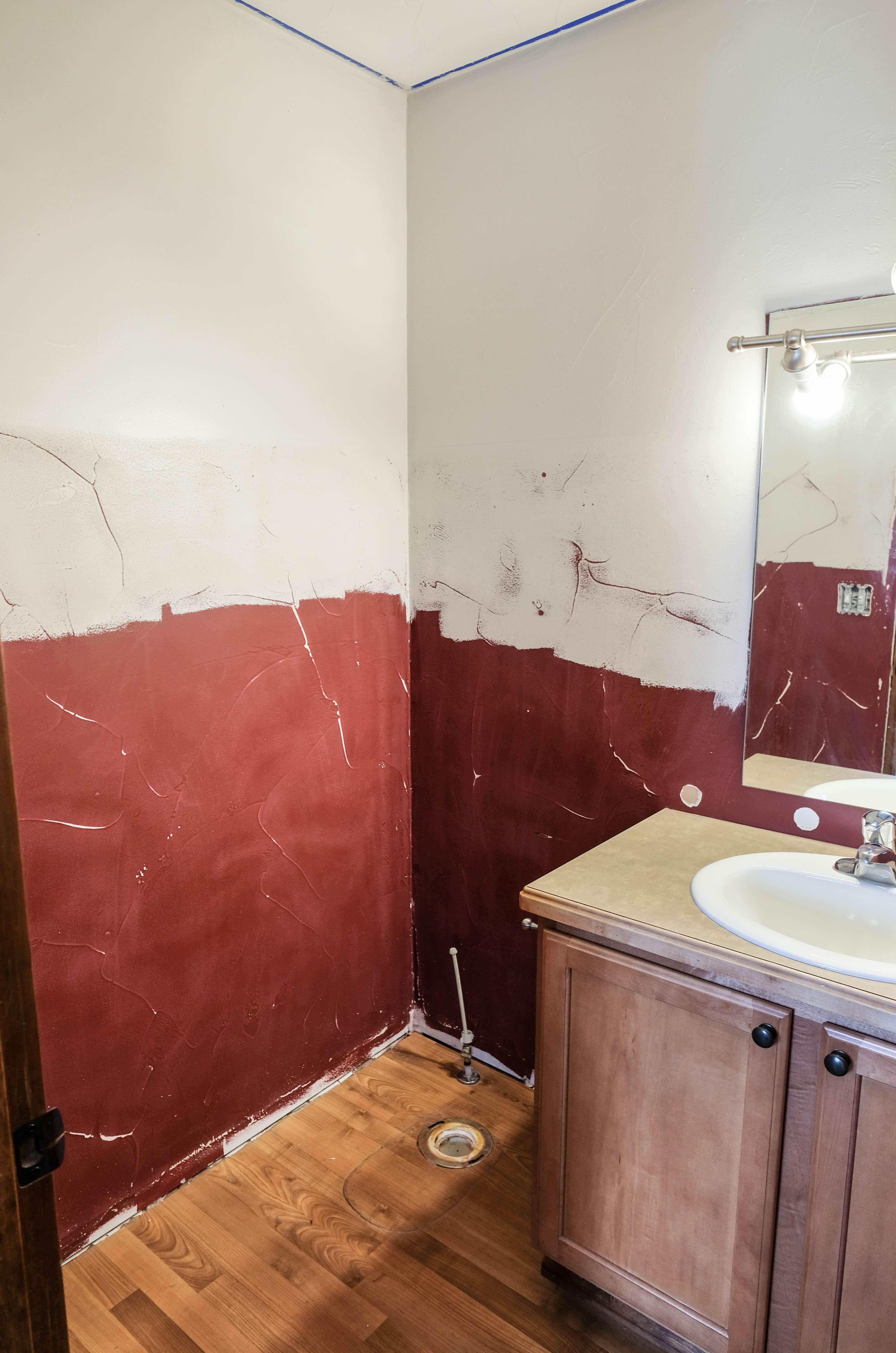 A halfbath in the middle of being painted and sanded in order to apply wallpaper