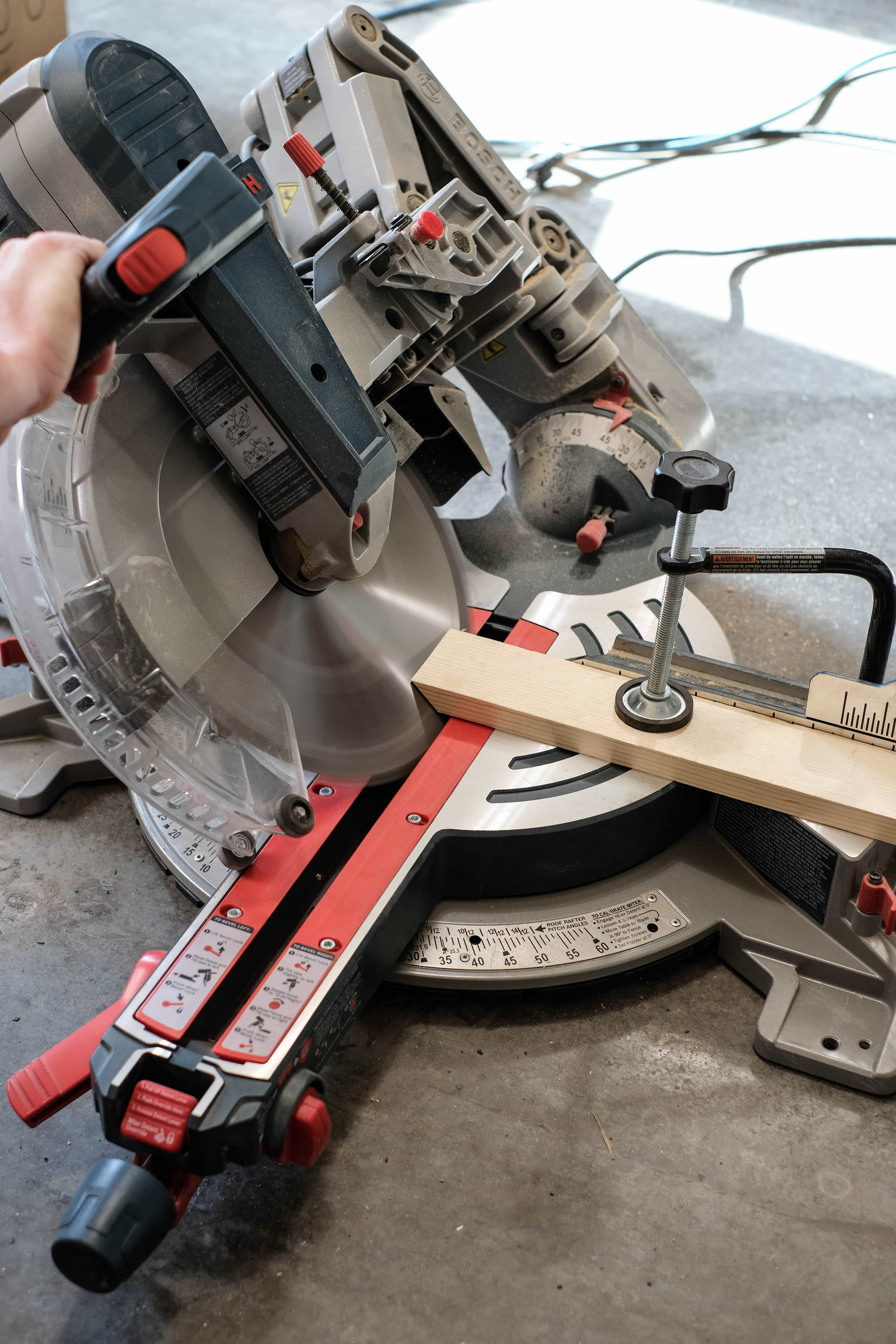 """Miter saw cutting a 1"""" x 3"""" pine board at a 45 degree angle"""