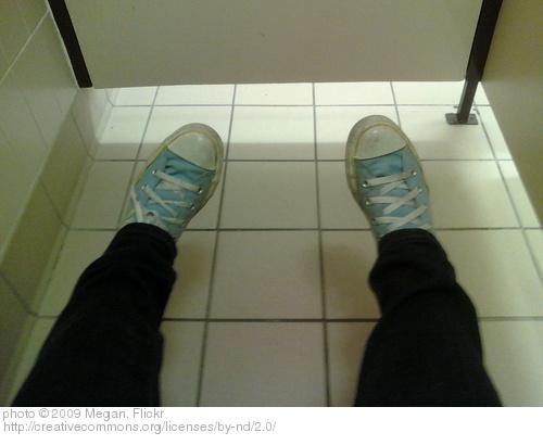 feet in bathroom stall