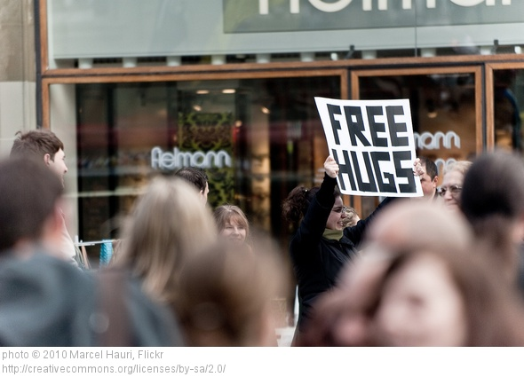 Woman with sign giving free hugs