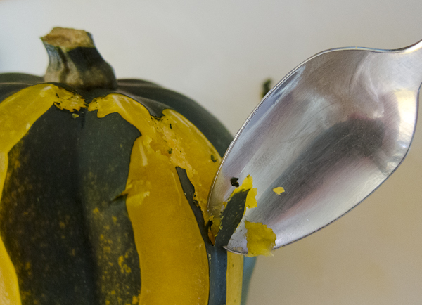 A photo shows how a spoon can be used to peel an acorn squash once it's been boiled.