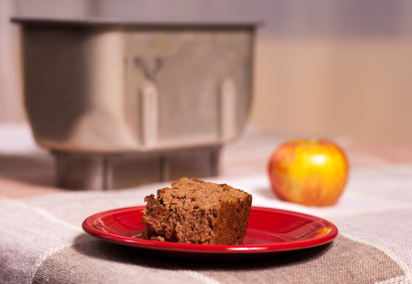 Applesauce Bread Pudding on a red plate, with apple and bread machine bucket in background