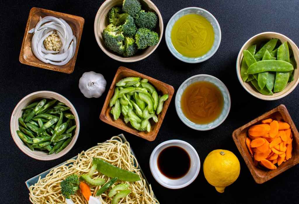 Filipino Vegetable Pancit Noodle ingredients with green beans, garlic, onions, brocolli, celery, pea pods, carrots, lemon, soy sauce, oyster sauce, sesame oil, olive oil