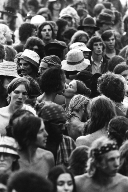 """Watkins Glen, NY. July 28th, 1973. Couple kissing in the middle of the crowd. The Summer Jam at Watkins Glen was a 1973 rock festival which once received the Guinness Book of World Records entry for """"Largest audience at a pop festival."""" An estimated 600,000 rock fans came to the Watkins Glen Grand Prix Raceway outside of Watkins Glen, New York on July 28, 1973, to see The Allman Brothers Band, Grateful Dead and The Band perform. Similar to the 1969 Woodstock Festival, an enormous traffic jam created chaos for those who attempted to make it to the concert site. Long and narrow country roads forced fans to abandon their vehicles and walk 5–8 miles on that hot summer day. 150,000 tickets were sold for $10 each, but for all the other people it was a free concert. The crowd was so huge that a large part of the audience was not able to see the stage; however, twelve huge sound amplifiers, installed courtesy of legendary promoter Bill Graham, allowed the audience to at least hear."""