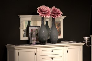 A chest of drawers with two vases on it.