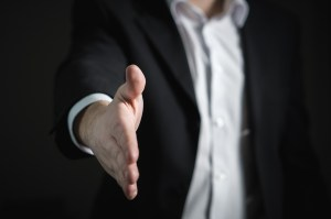 A man extending his hand for a handshake.