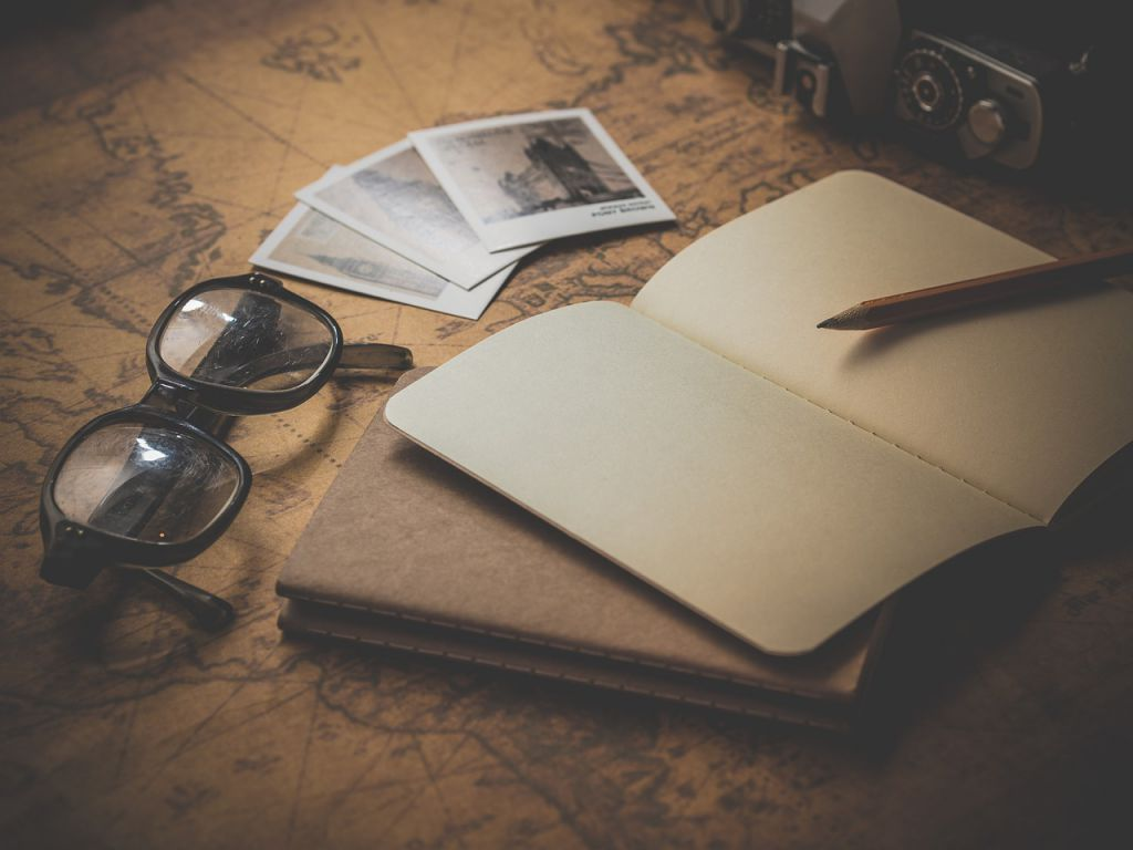 A notebook and a pencil next to photographs on top of a map.