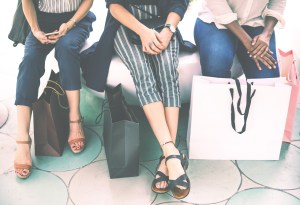 Three women with shopping boxes sitting next to each other.