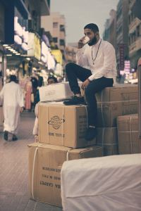 A guy lounging on a bunch of cardboard boxes, looking morosely into the distance. Just think about how much you'll help the environment if you use plastic bins - these cardboard boxes are going to fill the landfills.